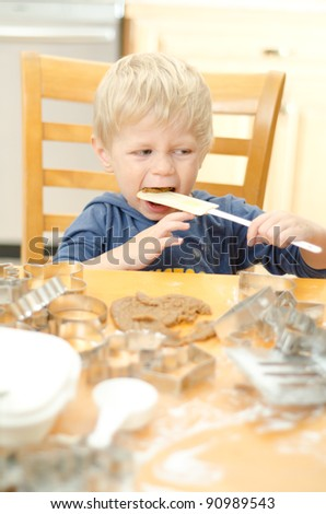 Young boy using cutouts and mixing dough to make gingerbread cookies. - stock photo
