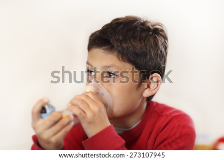Young boy using inhaler on white background - with shallow depth of field - stock photo