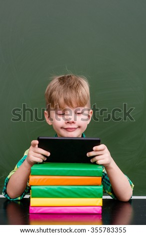 Young boy using tablet computer in classroom