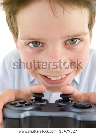 Young boy using videogame controller smiling - stock photo