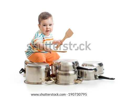 young boy using wooden spoons to bang pans drumset - stock photo