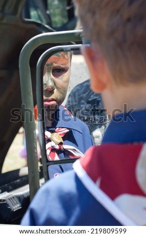 Young boy views his image after having his face painted in camouflage - stock photo
