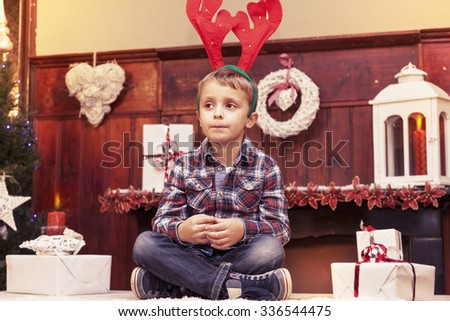 young boy waiting for santa claus sitting on the table - stock photo