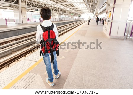 Young boy waiting for sky train in Bangkok, Thailand - stock photo