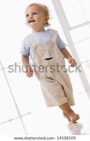 Young boy walking indoors smiling - stock photo