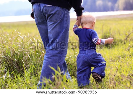 Young boy walking with his father in a grassy field. - stock photo