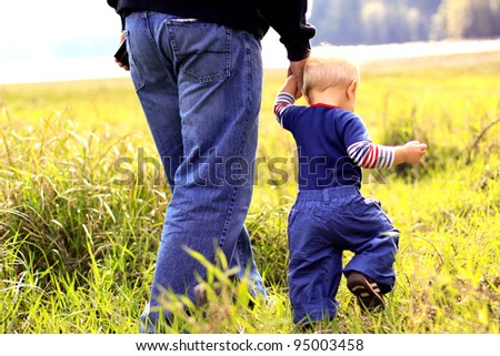 Young boy walking with his father in a grassy field.