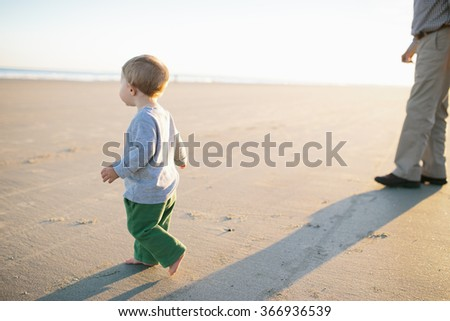 Young boy walks on beach during sunset with adult male in the background  - stock photo
