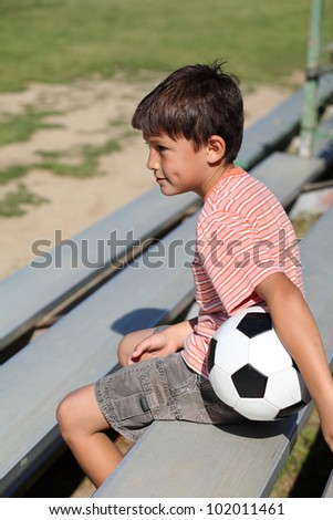 Young boy watches a sports game from the bleachers with a soccer ball under his arm - stock photo