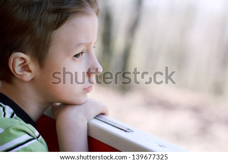 Young boy watching out from window, childhood - stock photo