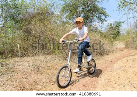 Young boy wear blue jean ride an vintage color old bicycle on the stone rough road on the dry hill in summer time with strong sunlight.
