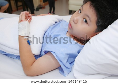 Young boy wear patient suit  in hospital bed - stock photo