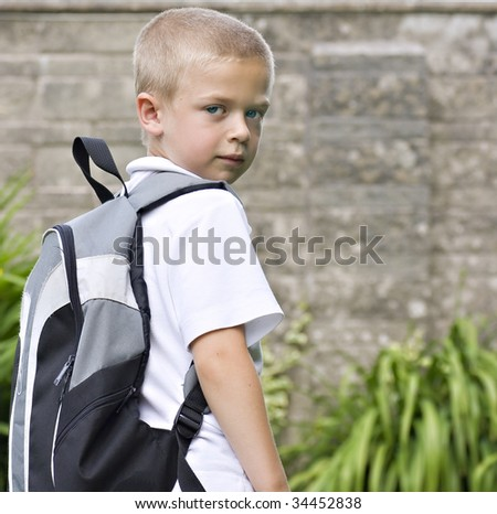 Young boy wearing a backpack ready for school