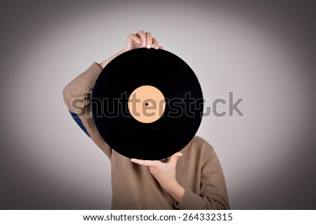 Young boy wearing a brown sweater covering his face with the vinyl record. Isolated on gray background and added vignette. Vintage style photo - stock photo