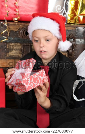 Young boy wearing a christmas hat dissapointed with gift - stock photo