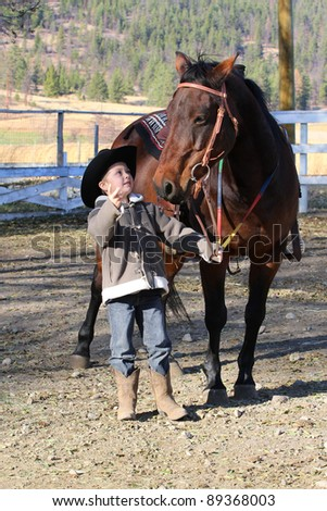 Young boy wearing a cowboy hat with his horse - stock photo