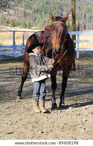 Young boy wearing a cowboy hat with his horse