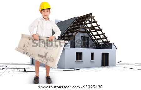 Young boy wearing a yellow safety helmet and holding blueprints with a house and blueprints at the background - stock photo