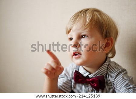 Young Boy Wearing Bow Tie and Pointing to the Side Against Plain Wall, as if in Conversation - stock photo