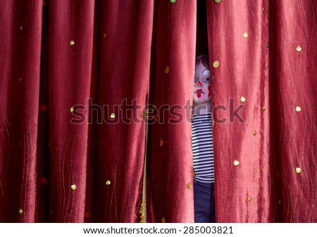 Young Boy Wearing Clown Make Up Peering Out Through Opening in Red Stage Curtains - stock photo