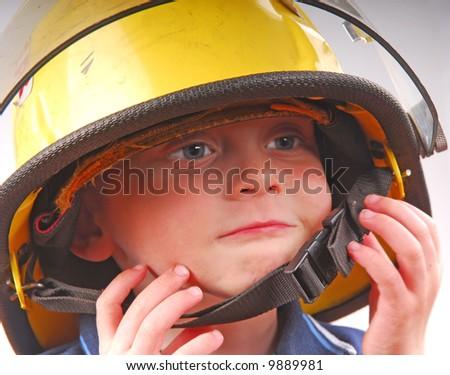 Young Boy Wearing Fireman's Helmet - stock photo