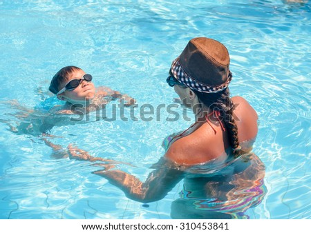 Young boy wearing goggles learning to swim with his mother in a swimming pool, view from behind the woman of his face and determined expression - stock photo