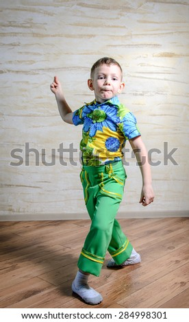 Young Boy Wearing Green Pants and Floral Print Shirt Snapping Fingers and Performing Traditional Dance in Studio - stock photo
