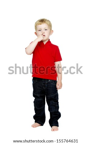 Young boy wearing jeans and a red T-shirt stood isolated on a white background picking his nose looking into the camera