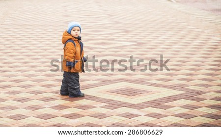 Young boy wearing stylish warmly dressed brown jacket and dark blue trousers against pavement , full length portrait texture Male look at camera Empty space for inscription  - stock photo
