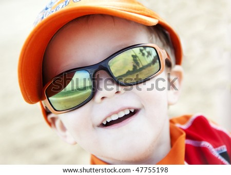 Young Boy Wearing Sunglasses Reflecting the Beach and Palm Trees - stock photo