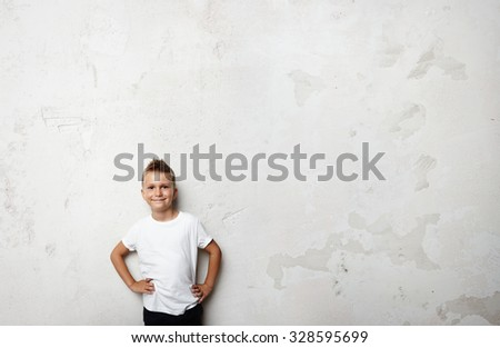 Young boy wearing white tshirt and smiling on the concrete wall background - stock photo