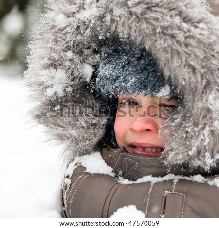 Young boy wearing winter jacket with furry hood playing in snow - stock photo
