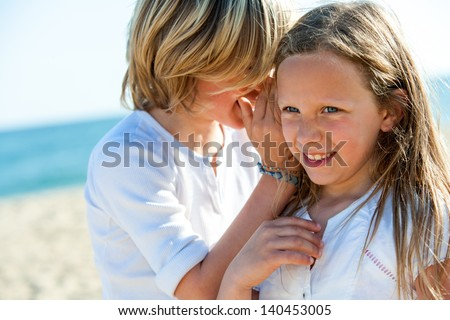 Young boy whispering secrets to girl on beach. - stock photo