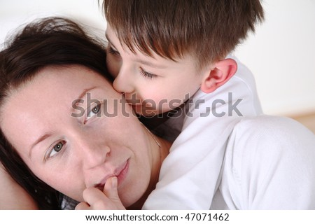 young boy whispers her mother in Ears - stock photo