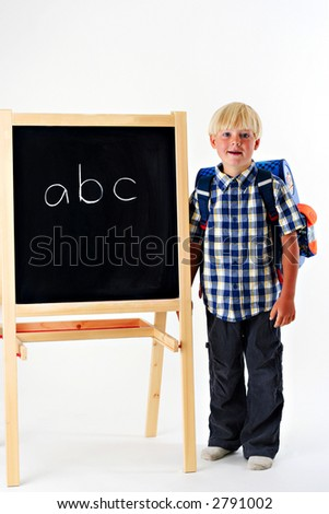 Young boy with a backpack standing next to a blackboard with the letters A B C - stock photo