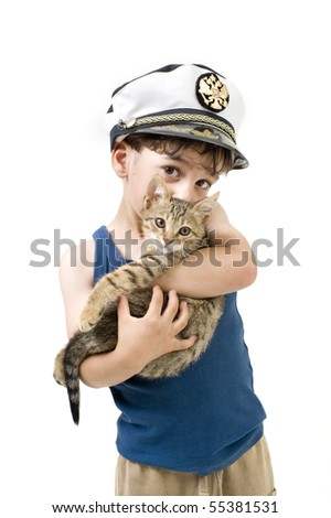 young boy with a captain hat holding a kitten - stock photo