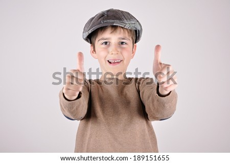 Young boy with a newsboy cap showing thumbs up - stock photo