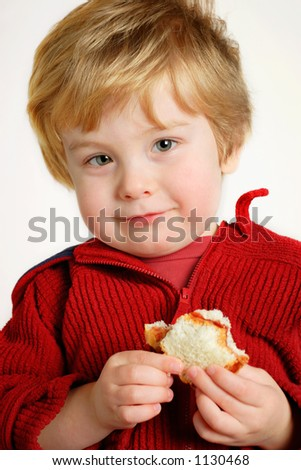 Young boy with a peanut butter and jelly sandwich (focus is on the boy's face - stock photo