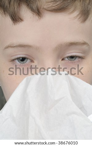 Young boy with a tissue having a cold close up