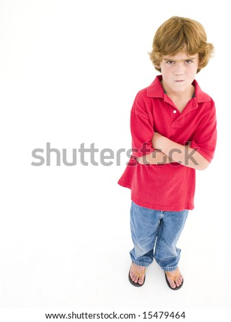 Young boy with arms crossed scowling - stock photo