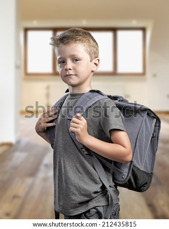 Young boy with backpack isolated on white background ready to go back to school - stock photo