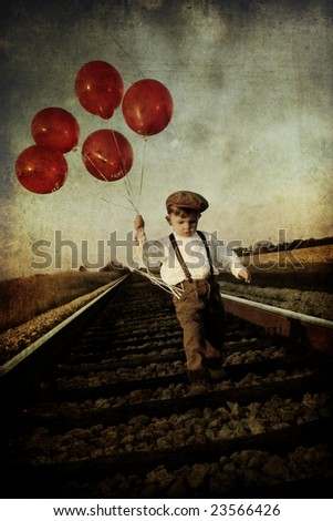 Young Boy with Balloons on Railroad Tracks - stock photo