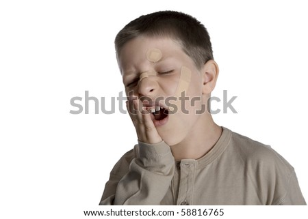 Young boy with band aids on face and hurting, studio shot isolated on white background - stock photo