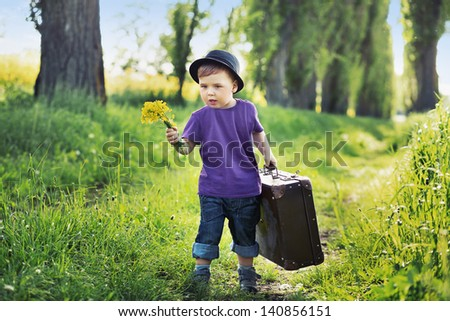 Young boy with big suitcase - stock photo