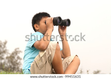 Young boy with binoculars .