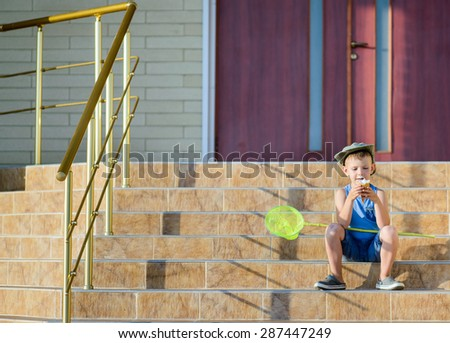 Young Boy with Bug Net Enjoying Ice Cream on Front Steps of Home Sitting in Bright Summer Sunshine - stock photo