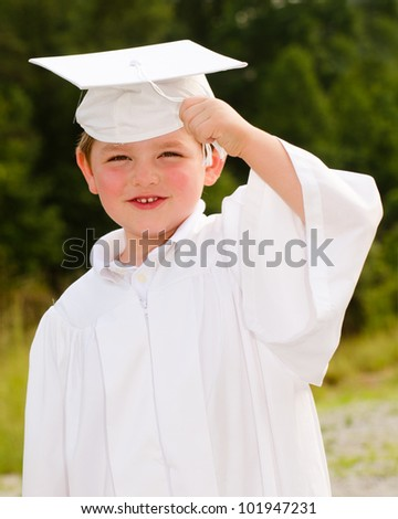 Young boy with cap and gown for preschool graduation - stock photo