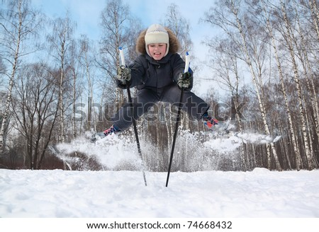 Young boy with cross-country skis and poles jumps and tongue out inside winter forest at sunny day - stock photo