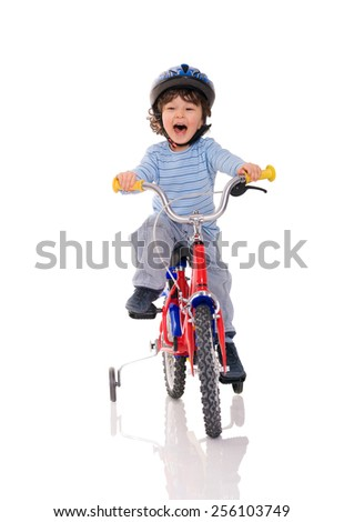 young boy with curly brown hair happily riding on a bicycle on isolated background