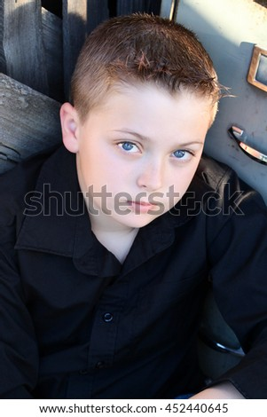 Young boy with deep blue eyes sitting against rustic background - stock photo